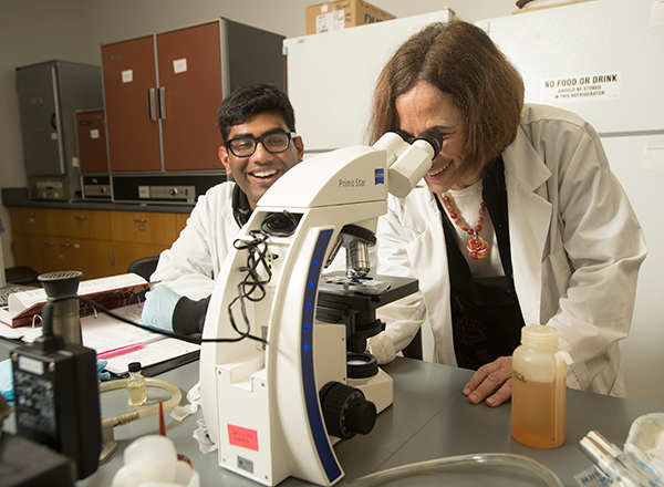 Professor Jill Adler-Moore works in the lab with a student.
